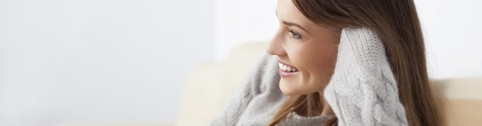 Happy young woman watching television on sofa