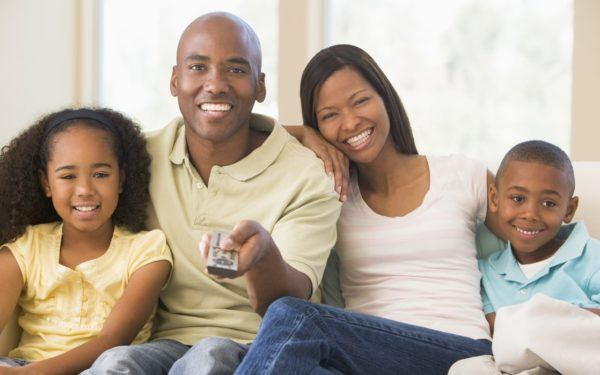 Smiling family sitting holding remote control