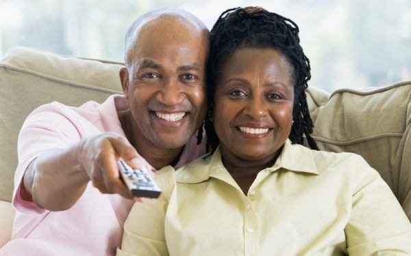 Couple relaxing in living room holding remote control and smiling