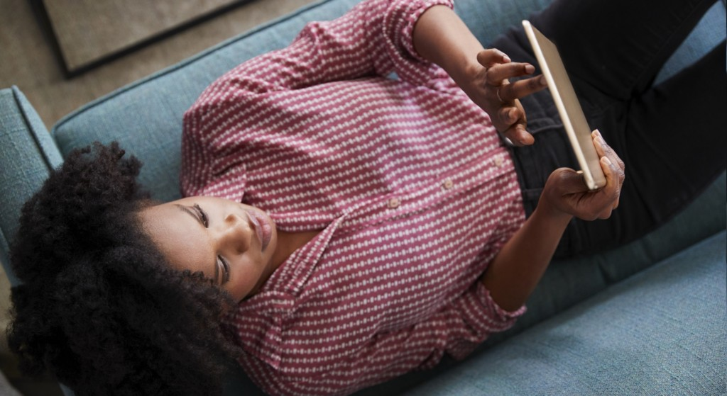 Overhead View Of Woman Lying On Sofa At Home Watching Movie On Digital Tablet