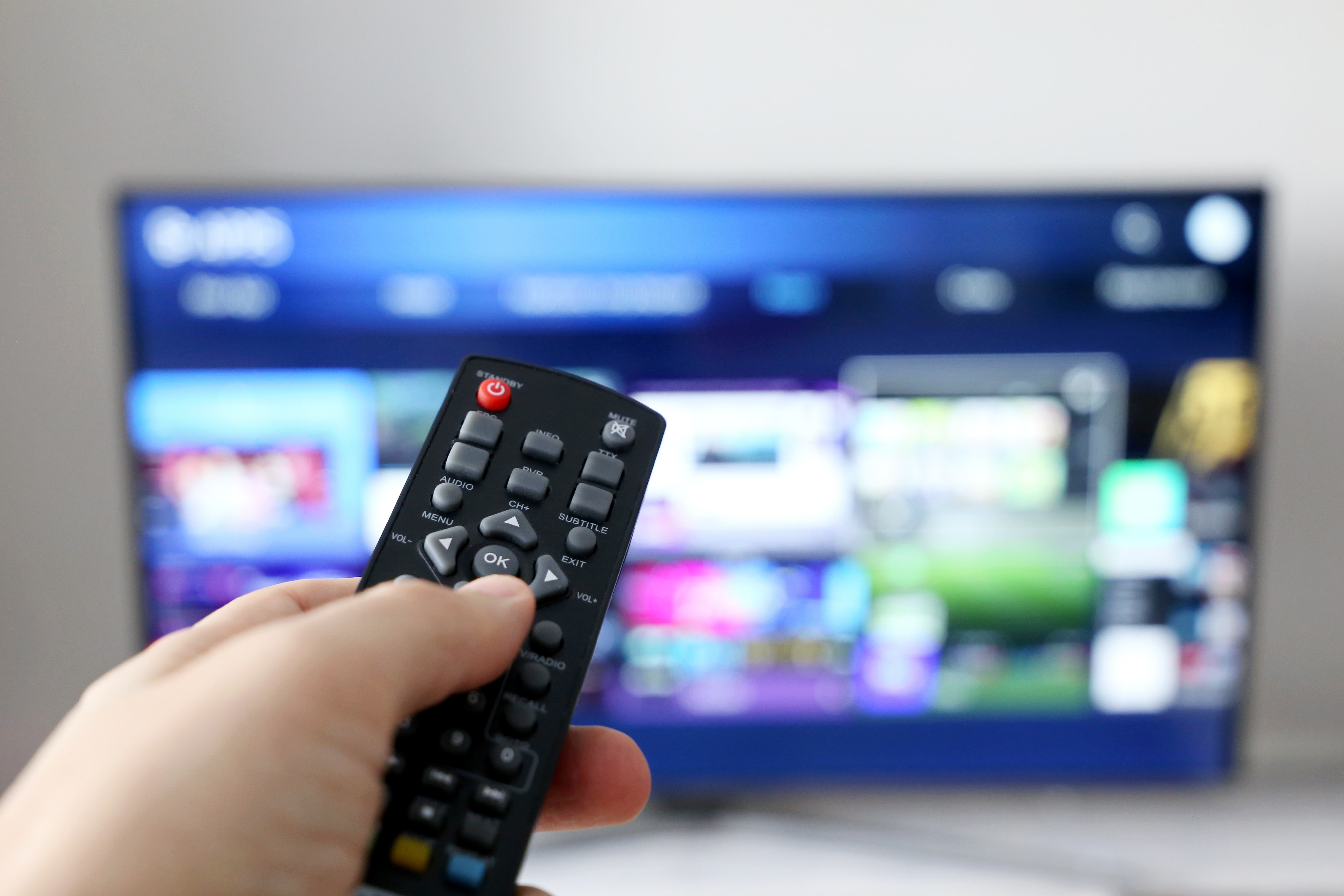 Hand holding a remote control in front of a TV